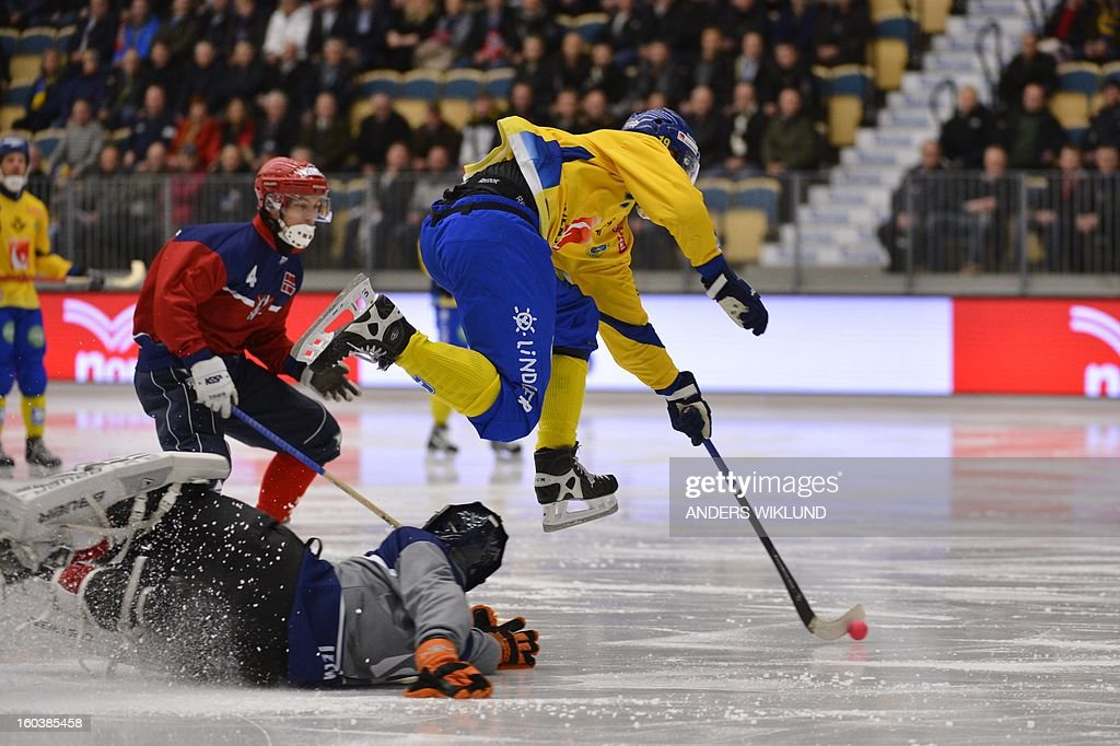 Sweden's Patrik Nilsson (R) jumps over Norway's goalie Christopher Smerkerud during the Bandy World Championship match between Sweden and Norway in Vanersborg, Sweden, on January 30, 2013.