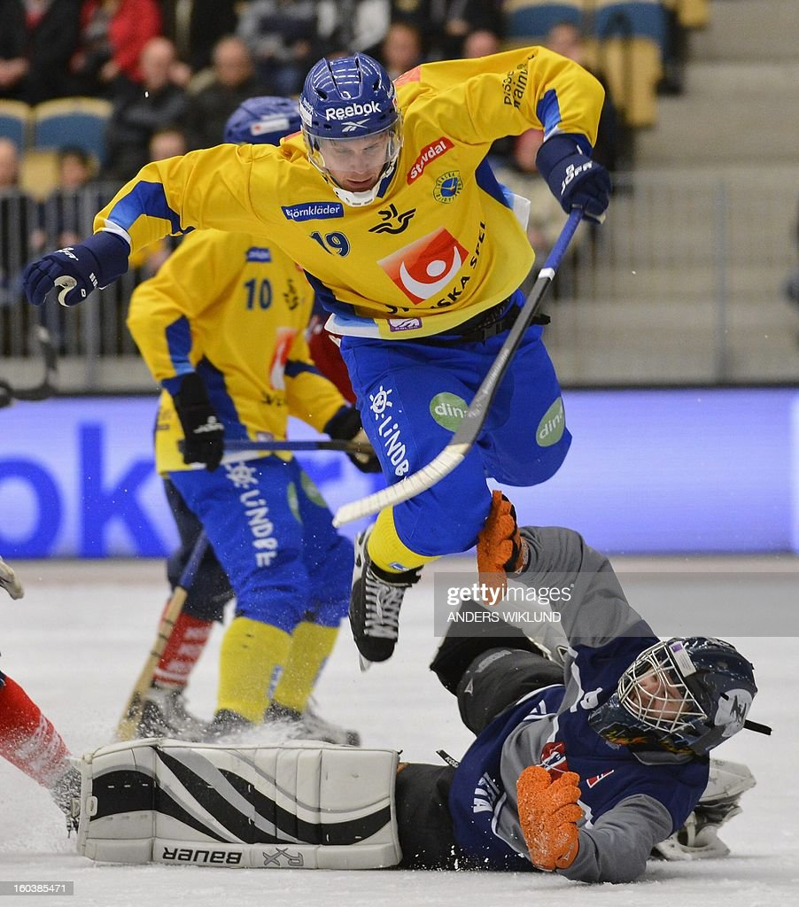 Sweden's Patrik Nilsson (top) jumps over Norway's goalie Christopher Smerkerud during the Bandy World Championship match between Sweden and Norway in Vanersborg, Sweden, on January 30, 2013.