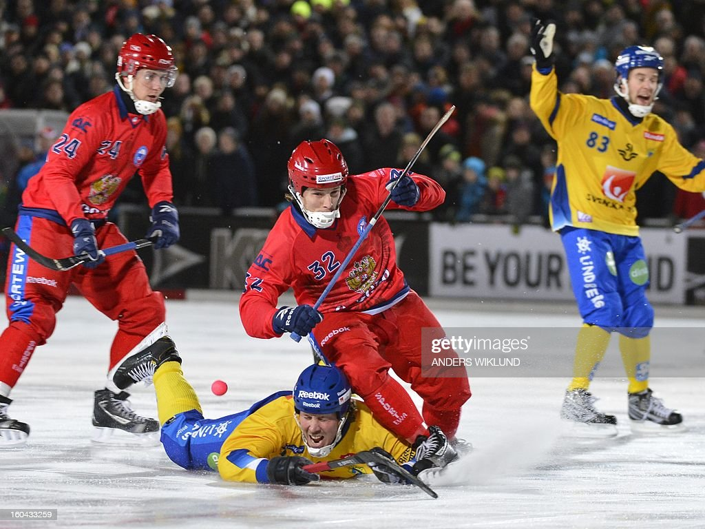 Sweden's Patrik Nilsson (C) lies on the ice and Russia's Pavel Bulatov is above him during the Bandy World Championship match between Sweden and Russia in Goteborg, Sweden, on January 31, 2013.
