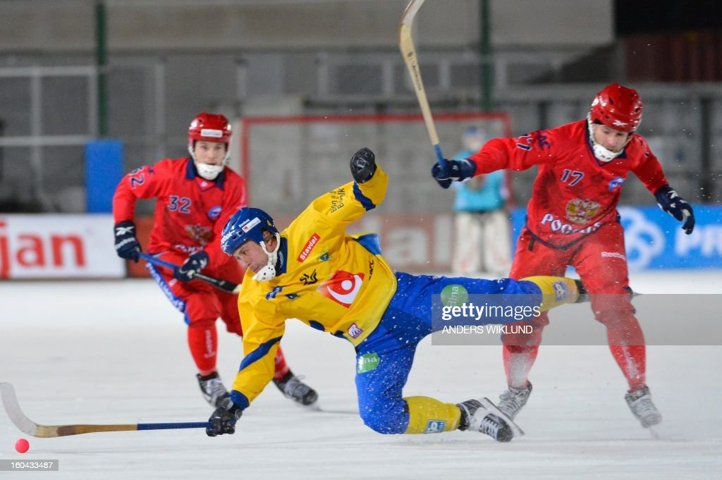 Sweden's Per Hellmyrs (C) falls in front of Russia's Pavel Bulatov (L) and Dmitri Saveliev (R) during the Bandy World Championship match between Sweden and Russia in Goteborg, Sweden, on January 31, 2013.