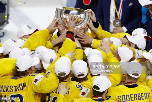 TOPSHOT Sweden's players celebrate with the trophy after winning the IIHF Men's World Championship Ice Hockey final match between Canada and Sweden...