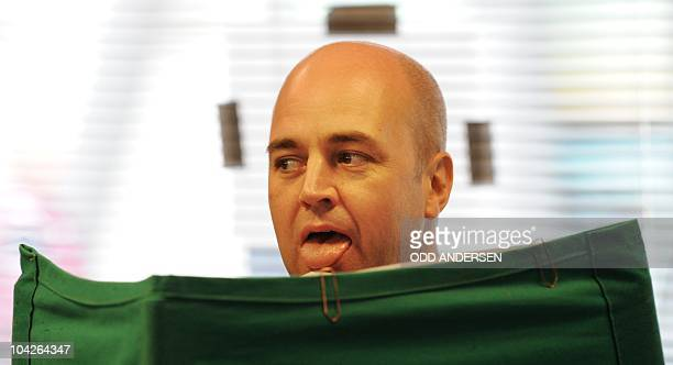 Sweden's Prime minister and leader of the Moderaterna party Fredrik Reinfeldt licks the envelope with his ballot as he votes in the Stockholm suburb...