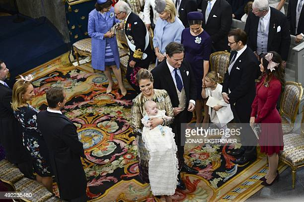 Sweden's Prince Madeleine holds her newly baptised son Prince Nicolas as her husband Chris O'Neill looks on next to Queen Silvia King Carl XVI Gustaf...
