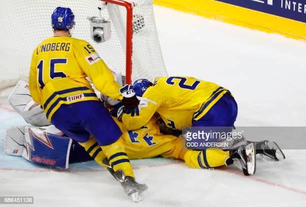 Sweden's William Nylander and Sweden's Oscar Lindberg celebrate with Sweden's goalie Henrik Lundqvist after the penalty shootout of the IIHF Men's...