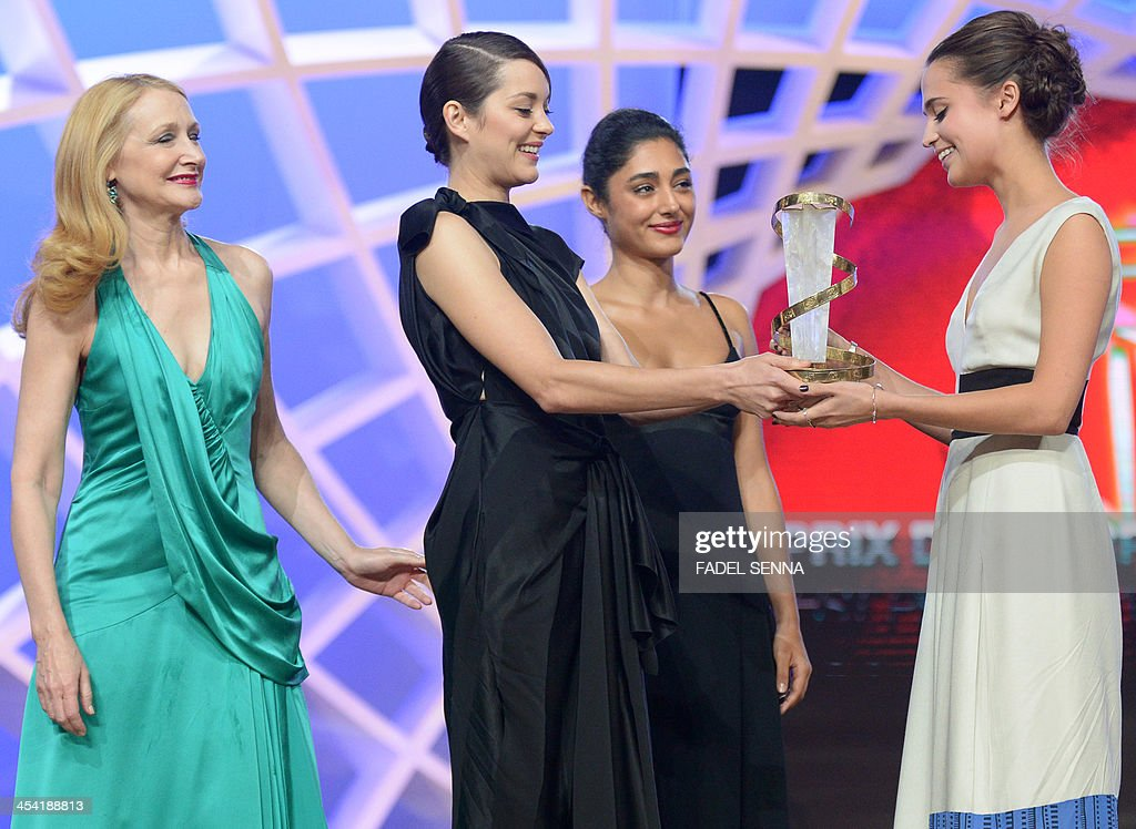 Swedish actress Alicia Vikander (R) receives the prize for the best prefomance by an actress from Marion Cotillard (2nd L), Golshifteh Farahani (2nd R), and Patricia Clarkson (L) during the closing ceremony of the 13th Marrakech International Film Festival on December 7, 2013 in Marrakech.