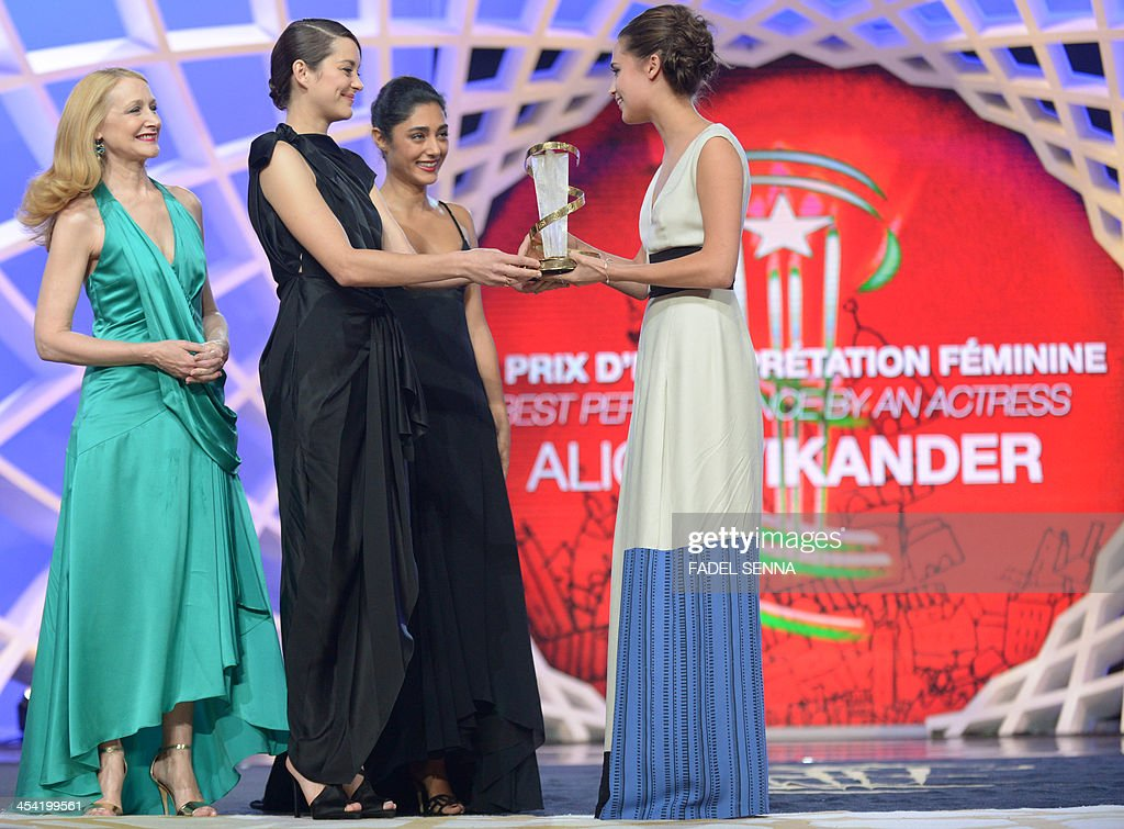 Swedish actress Alicia Vikander (R) receives the prize of the best prefomance by an actress from French actress Marion Cotillard (2nd L), Golshifteh Farahani (2nd R) and Patricia Clarkson (L) during the closing ceremony of the 13th Marrakech International Film Festival on December 7, 2013 in Marrakech.
