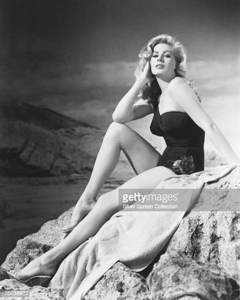Swedish actress Anita Ekberg poses on a rocky shore circa 1955