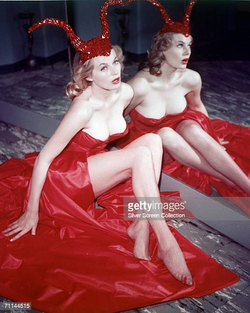 Swedish actress Anita Ekberg sitting by a mirror in a red satin dress and a sequinned devilhorn cap circa 1956