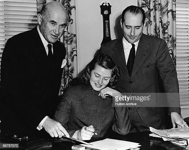Swedish actress Ingrid Bergman sits at a desk and prepares to sign a document as Polishborn studio chief Samuel Goldwyn points with a letter opener...