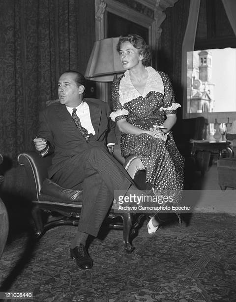 Swedish actress Ingrid Bergman wearing a polkadotted dress portrayed while smoking a cigarette sitting on the arm of an armchair close to her husband...