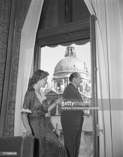 Swedish actress Ingrid Bergman wearing a polkadotted dress portrayed with Roberto Rossellini while looking out of the hotel window the Salute church...