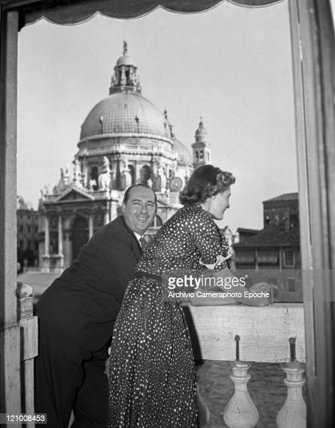 Swedish actress Ingrid Bergman wearing a polkadotted dress portrayed with Roberto Rossellini while standing on the hotel terrace the Salute church in...