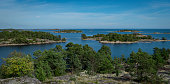 Archipelago in Sweden taken from a small mountain on an island. Some blue water with many small islands and a blue cloudy sky.