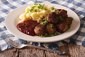 Swedish cuisine: meatballs, lingonberry sauce with potato garnish on a plate close-up. horizontal