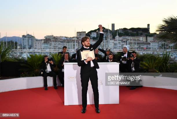 Swedish director Ruben Ostlund celebrates with his trophy during a photocall on May 28 2017 after he won the Palme d'Or for his film 'The Square' at...