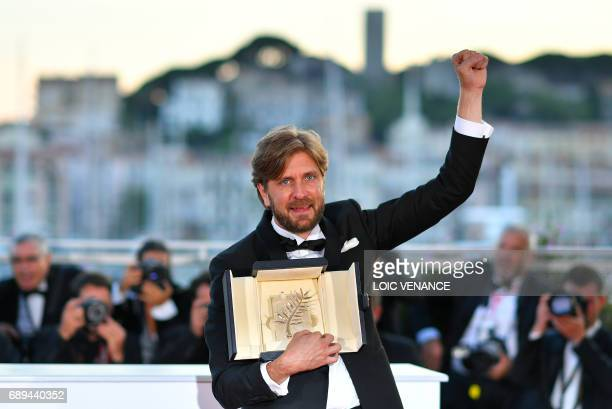 Swedish director Ruben Ostlund celebrates with his trophy on May 28 2017 during a photocall after he won the Palme d'Or for his film 'The Square' at...