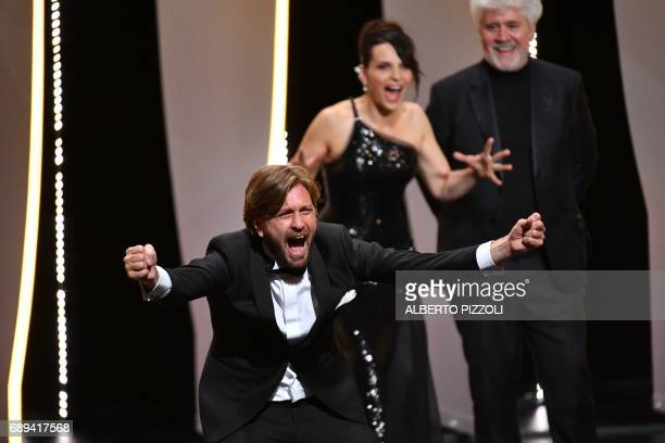 Swedish director Ruben Ostlund reacts on stage as French actress Juliette Binoche and Spanish director and President of the Feature Film Jury Pedro...