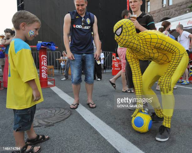 A Swedish fan dressed as a super hero plays with an Ukrainian boy in a fan zone in Kiev on June 17 2012 during the Euro 2012 football championships...