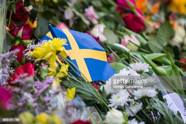 Swedish flag among the flowers is left outside of a store on Drottninggatan on April 9 2017 in Stockholm Sweden An Uzbek man has been arrested held...