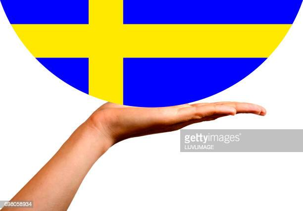 Swedish Flag in a hemisphere, on the palm of a hand.
