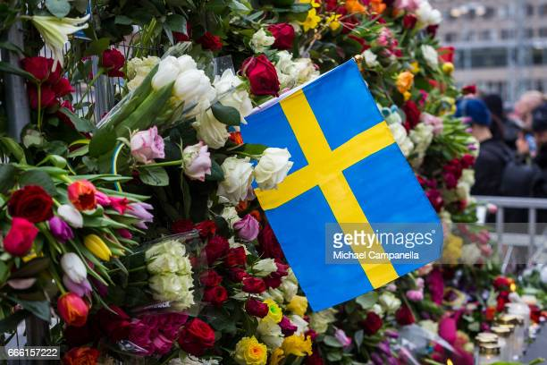 Swedish flag placed next to a wall of flowers at the scene of the terrorist truck attack in downtown Stockholm on April 8 2017 in Stockholm Sweden