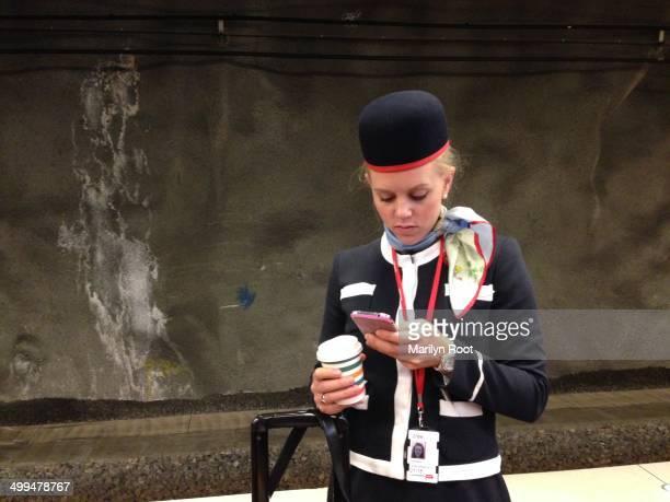 Swedish flight attendant with coffee checking phone