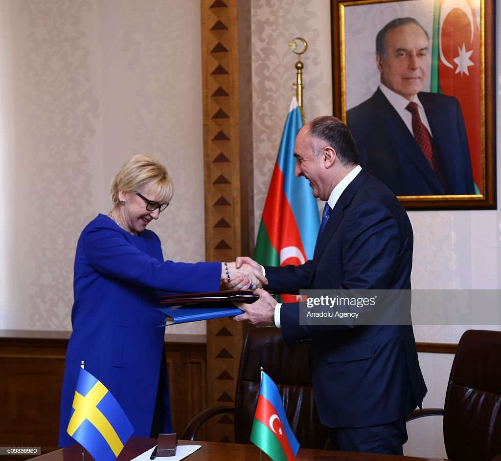 Swedish Foreign Minister Margot Wallstrom (L) and Azerbaijani Foreign Minister Elmar Memmedyarov (R) exchange files after an inter-delegations meeting in Baku, Azerbaijan on February 10, 2016.