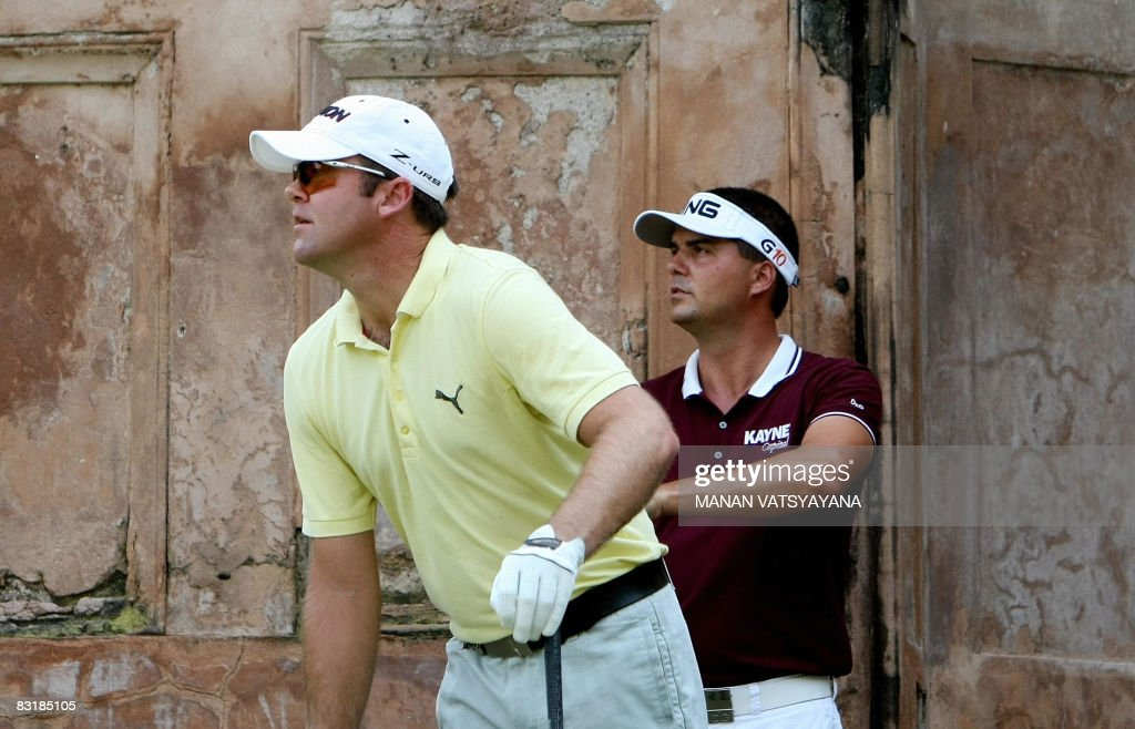 Swedish golfer Daniel Chopra and New Zealand's Mark Brown watch a teeoff during the first round of the Hero Honda Indian Open at The Delhi Golf Club...