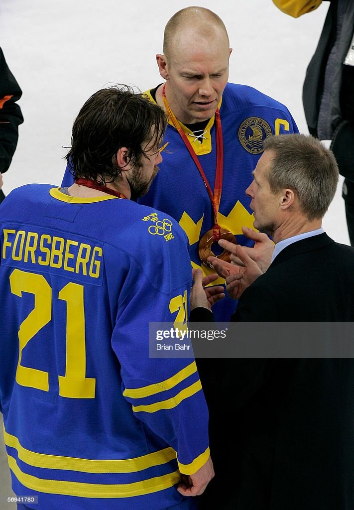 Swedish head coach Bengt Ake Gustafsson talks with Peter Forsberg and Mats Sundin both of Sweden after Sweden defeated Finland 32 to win the gold...
