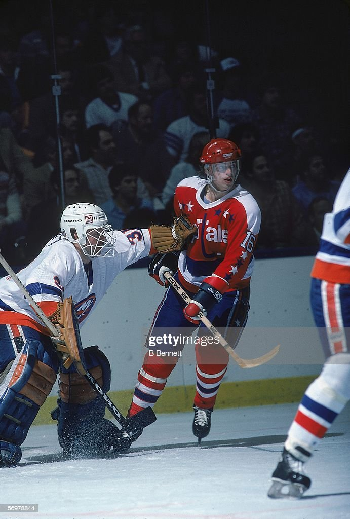 Swedish hockey player Bengt Gustafsson of the Washington Capitals skates near New York Islanders goalie Billy Smith during a game at Nassau Coliseum...