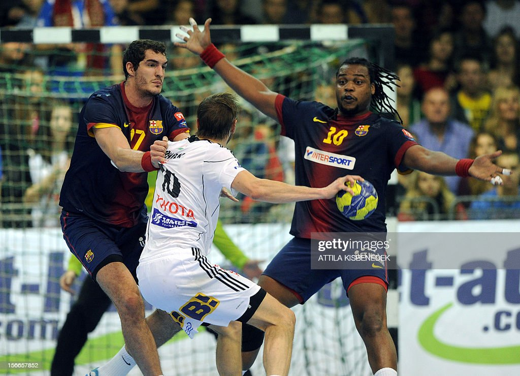 Swedish Jonas Erik Larholm (C) of Hungarian PICK-Szeged fights with Spanish FC Barcelona's Angel Montoro (L) and French Cedric Sorhaindo on November 18, 2012 in Szeged during their EHF Champions League match.