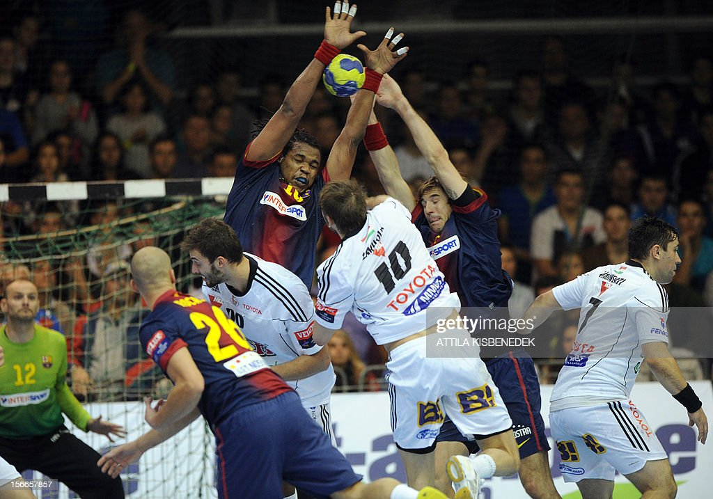 Swedish Jonas Erik Larholm (C) of Hungarian PICK-Szeged fights with Spanish FC Barcelona's French Cedric Sorhaindo (C-L) and Viran Morros (C-R) on November 18, 2012 in Szeged during their EHF Champions League match.