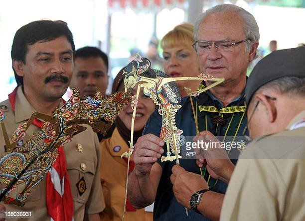 Swedish King Carl XVI Gustaf accompanied by Indonesian Youth and Sports Minister Andi Mallarangeng tries a Wayang Kulit a traditional puppet in...