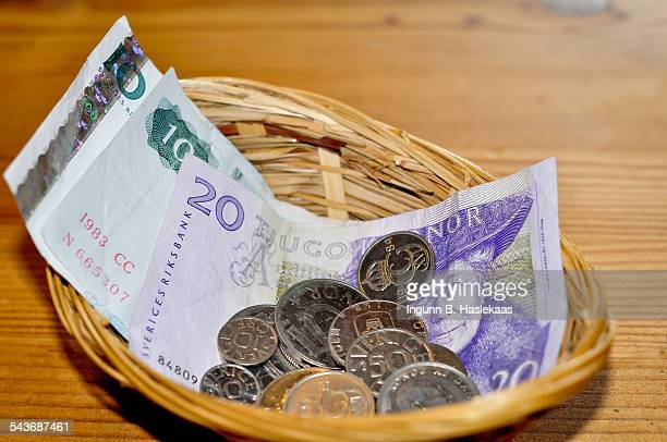 Swedish krone banknotes and coins in a little basket