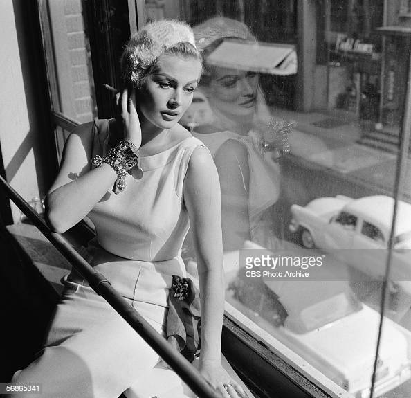 Swedish model and actress Anita Ekberg sits on a windowsill and looks out over a street during rehearsal for an episode of the television series...