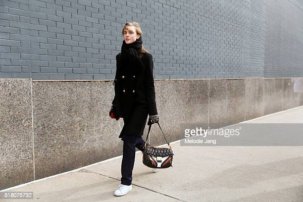 Swedish model Hedvig Palm wears a black peacoat and scarf and carries a Miu Miu quilted purse with zippers after the Jason Wu show at Spring Studios...