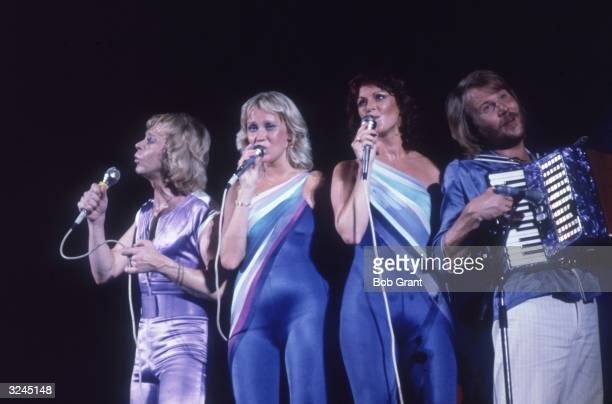 Swedish musical group ABBA performing on stage Bjorn Ulvaeus Agnetha Faltskog and AnniFrid Lyngstad sing while Benny Andersson plays the accordion...