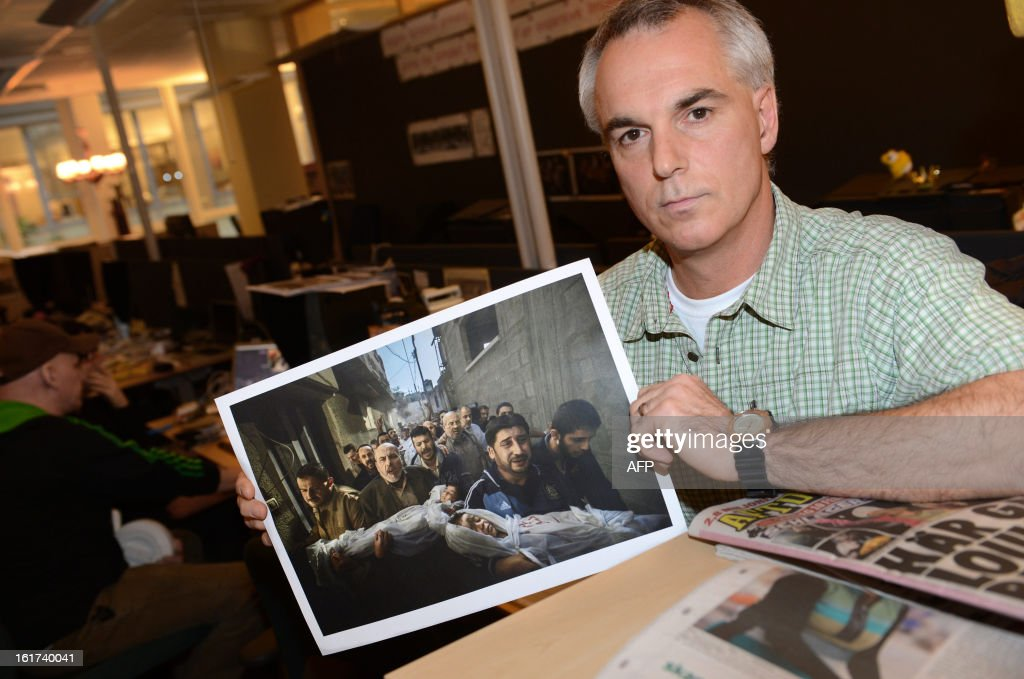 Swedish photographer Paul Hansen poses with the World Press Award winning picture of the Gaza conflict at the office of Swedish newspaper Dagens Nyheter in Stockholm, Sweden on February 15, 2013. The picture of men carrying the bodies of two dead children through a street in Gaza City was taken on November 20, 2012. The winner of the World Press Award 2013 were announced on February 15, 2013.