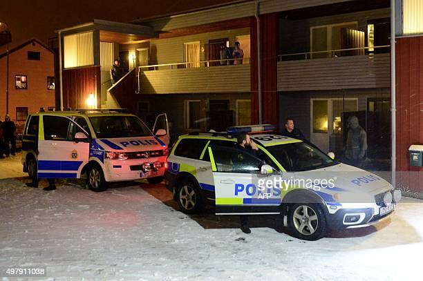 Swedish police stand by police cars outside a house used as a temporary shelter for asylum seekers in Boliden in northeastern Sweden on November 19...
