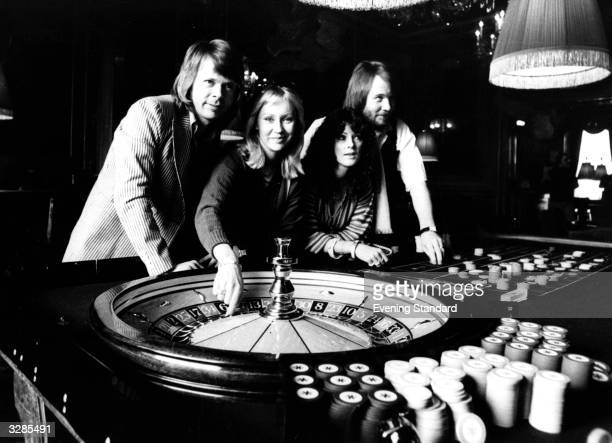 Swedish pop group Abba poised above a roulette wheel at a casino