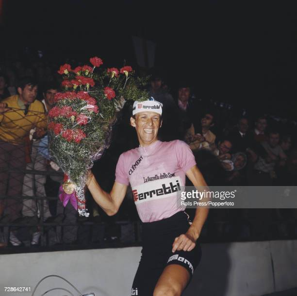 Swedish professional road race cyclist Gosta Pettersson pictured wearing the pink jersey holds a large bouquet of flowers in his hand after finishing...