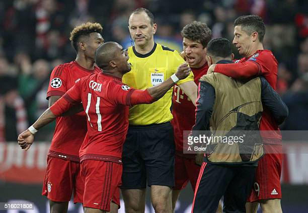 Swedish referee Jonas Eriksson is surrounded by Thomas Mueller of Bayern Muenchen and teammates David Alaba Douglas Costa Thiago and Robert...