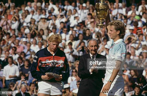 Swedish tennis player Stefan Edberg holds up the Gentlemen's Singles Trophy after defeating Boris Becker in the final of the Men's Singles tournament...