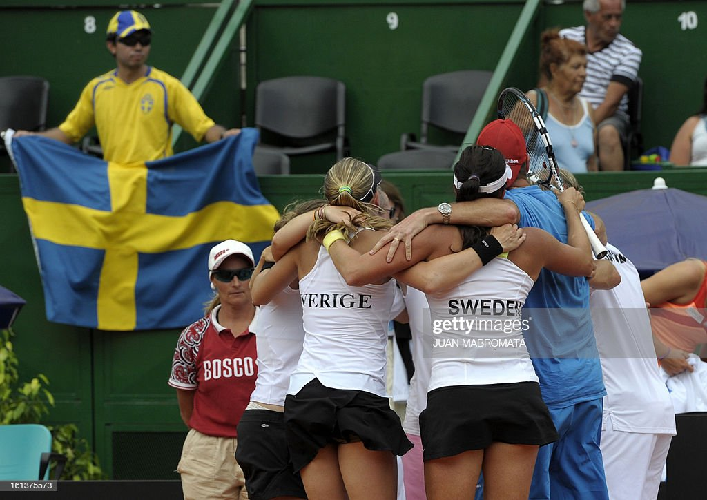 Swedish tennis players Johanna Larsson (L) and teammate Sofia Arvidsson celebrate with the team after defeating Argentine tennis players Maria Irigoyen and teammate Mailen Auroux by 6-4, 6-4 in their 2013 Fed Cup World Group II first round single tennis match at Parque Roca stadium in Buenos Aires on February 10, 2013. Sweden won by 3-2. AFP PHOTO / Juan Mabromata