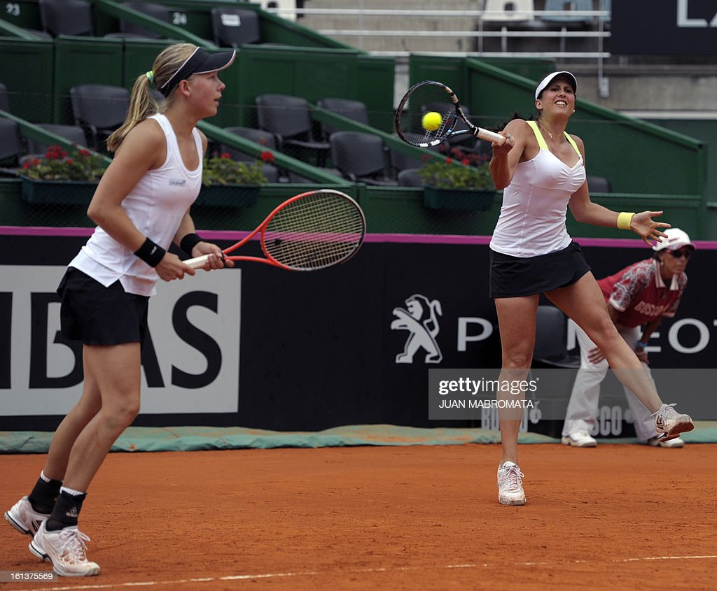 Swedish tennis players Sofia Arvidsson (R)returns the ball next to teammate Johanna Larsson to defeate Argentine tennis players Maria Irigoyen and teammate Mailen Auroux by 6-4, 6-4 in their 2013 Fed Cup World Group II first round single tennis match at Parque Roca stadium in Buenos Aires on February 10, 2013. Sweden won by 3-2. AFP PHOTO / Juan Mabromata