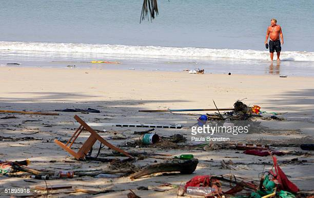Swedish tourist wades in the ocean along a garbage strewn beach December 27 2004 in Phuket Thailand A tsunami caused by an earthquake estimated to be...