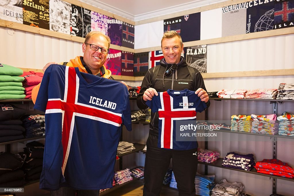 Swedish tourists hold Icelandic football jerseys in a shop in Reykjavik, on July 1, 2016. With a large part of its population in France for the Euro 2016, Iceland has pretty much come to a standstill these days, except for its tourism sector which is booming. / AFP / Karl Petersson / TO