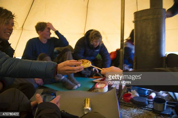 Swedish touristswarm up in their tent after a surfing session in Unstad beach in the Lofoten Islands within the Arctic Circle on April 17 2015...