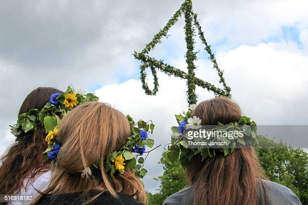 Swedish women with flowers in their hair looking at maypole during Swedish midsummer celebrations in Gothenburg, Sweden