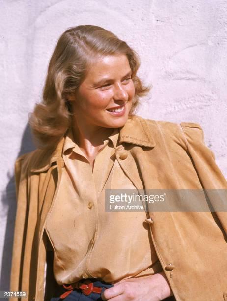 Swedishborn actor Ingrid Bergman smiles as she poses outdoors wearing a tan leather jacket circa 1945